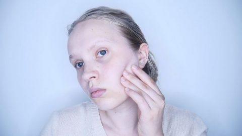 woman pressing face