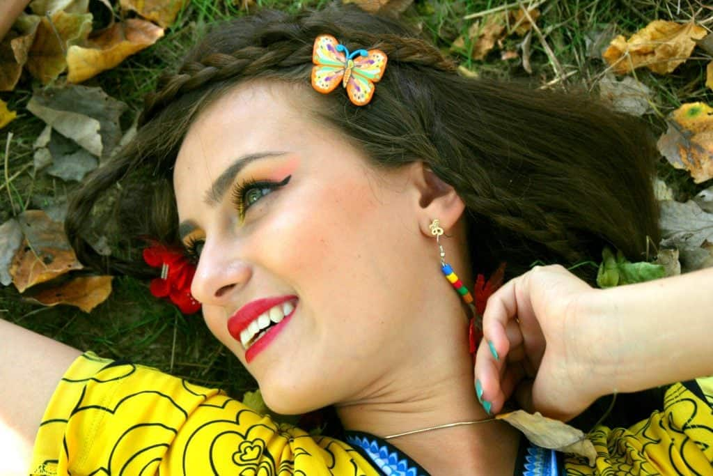 woman smiling as she lays on the grass