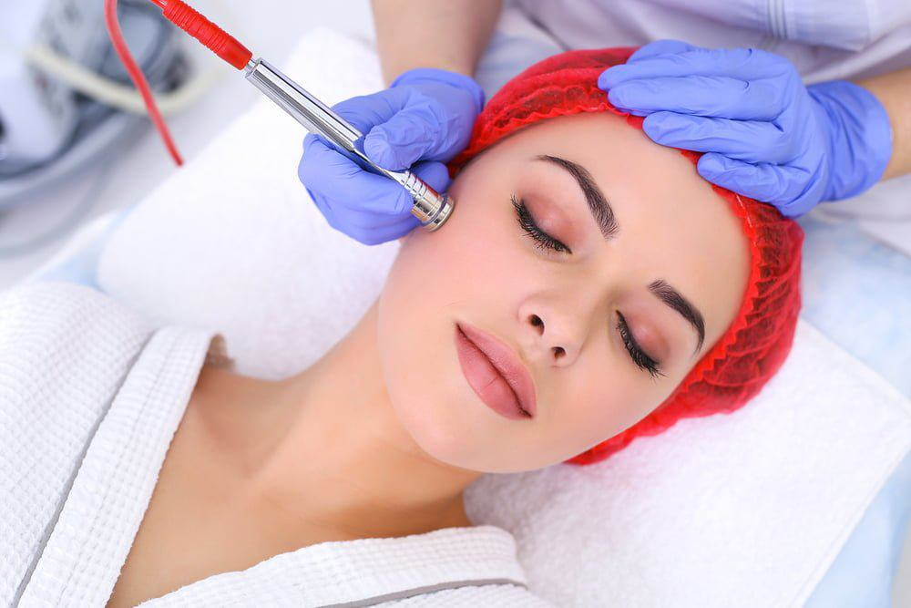 Frontal view of woman getting acne treatment with microdermabrasion machine