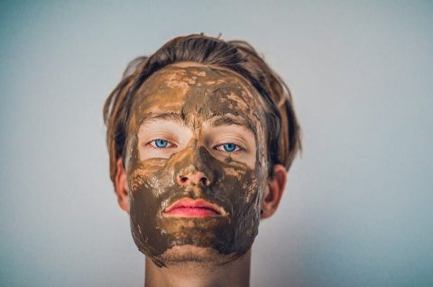 Man with mud mask on face