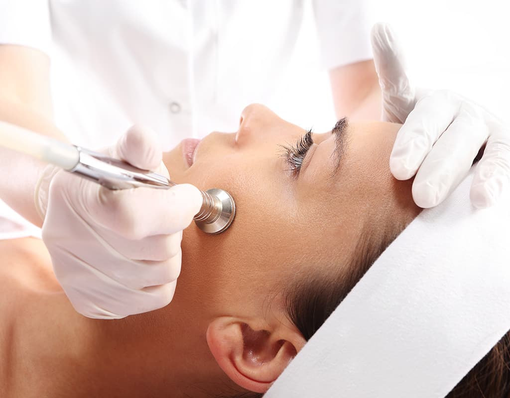 beautician using beauty tools to work on woman's face