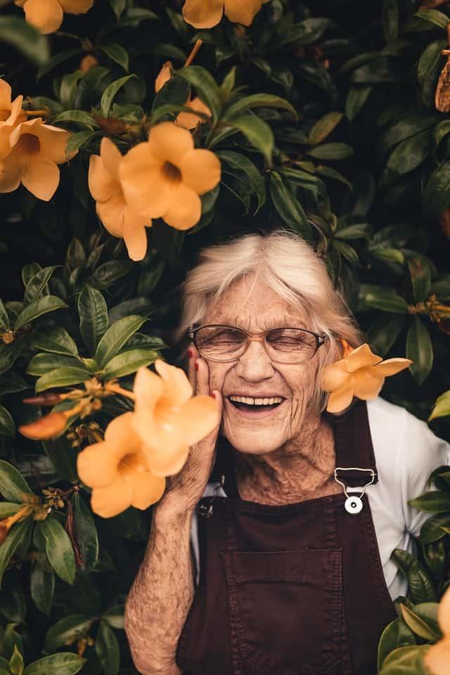 Elderly lady standing in a flower bush