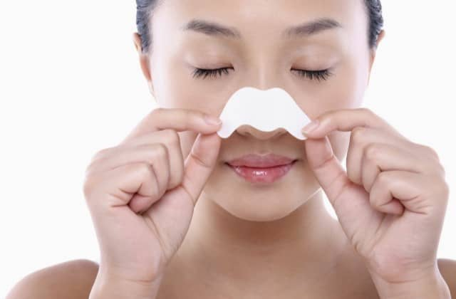 Young woman doing skincare, peeling off pore strip from her nose
