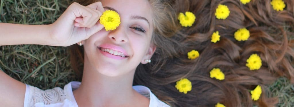 Girl smiling happily with yellow flower petals on her hair