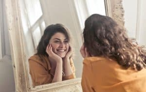 Happy woman holding her face while looking into the mirror