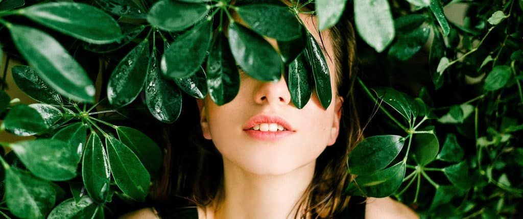 Woman's face covered by green plants - Reviews of BootsBotanics AgeDefense