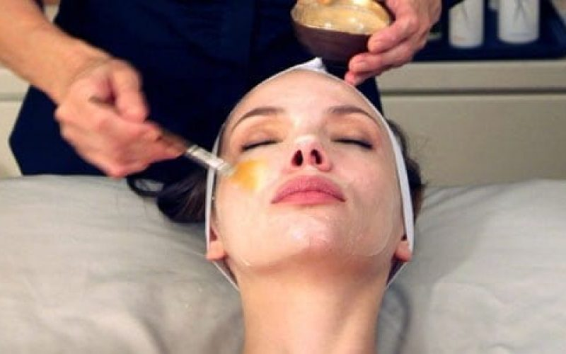 woman getting facial from male beautician