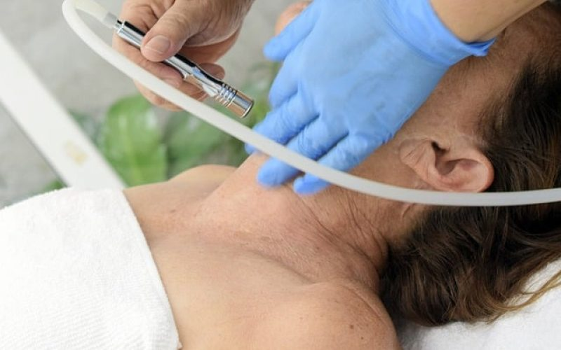 woman doing laser treatment on her face